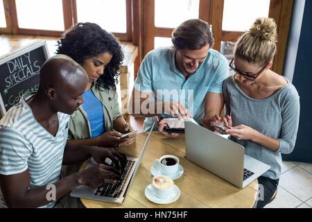 Les amis à l'aide d'un ordinateur portable, téléphone mobile et tablette numérique tandis que le café en café