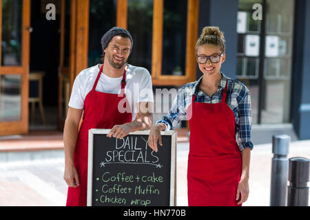 Portrait of smiling waitress and waiter standing avec menu Se connecter à l'extérieur conseil café Banque D'Images