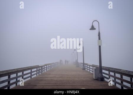 Silhouettes de personnes dans le brouillard sur l'Imperial Beach Pier. Banque D'Images