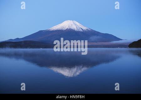 Vue de la nuit de ciel nuageux et le Mont Fuji de nuit du lac Yamanaka, préfecture de Yamanashi, Japon