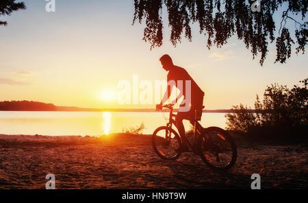 Garçon sur un vélo au coucher du soleil Banque D'Images