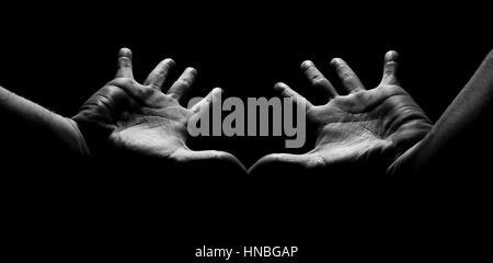 Tourné en noir et blanc des mains éclairées par la lumière du soleil Banque D'Images