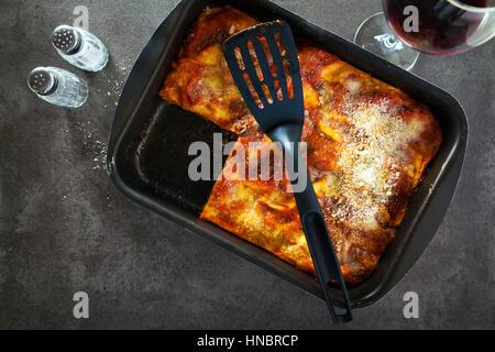 Lasagne aux italienne classique avec des légumes et le vin rouge dans le plat de cuisson sur un fond noir en gris, Banque D'Images