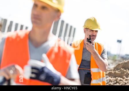 Travailleur homme d'âge moyen à l'aide de talkie-walkie avec collègue en premier plan at construction site Banque D'Images