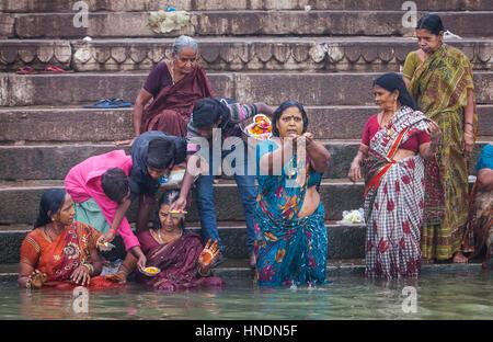 Pèlerins priant et baignade, dans les ghats du Gange, Varanasi, Uttar Pradesh, Inde. Banque D'Images