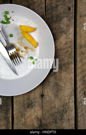 Vue aérienne des restes sur une plaque avec fourchette et couteau sur un fond de bois rustique Banque D'Images