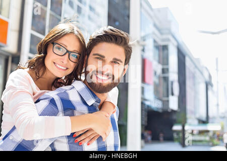 Portrait of happy man giving piggyback ride to woman in city Banque D'Images