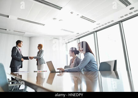 Businesspeople shaking hands in office Banque D'Images