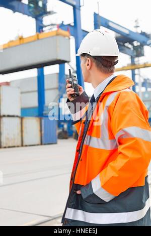 Homme d'âge moyen à l'aide de talkie-walkie en cour d'expédition Banque D'Images