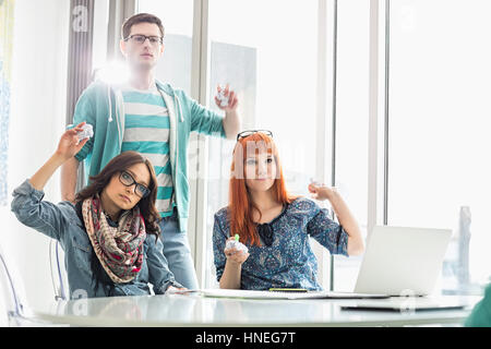 Angry woman throwing paper balls in creative office Banque D'Images