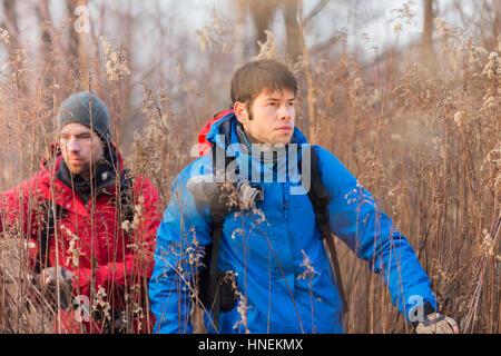 Les jeunes randonneurs marche à travers champ Banque D'Images
