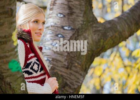 Young woman in vêtements chauds debout près des arbres dans le parc Banque D'Images