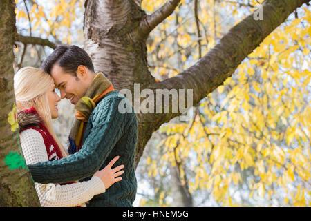 Vue latérale du jeune couple hugging près de l'arbre d'automne dans le parc Banque D'Images