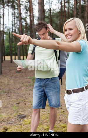Jeune femme en pointant à l'écart avec confus man holding map in forest Banque D'Images
