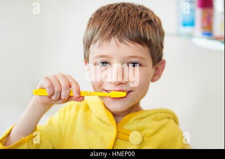 Garçon se brosser les dents dans la baignoire, smiling, fond gris clair Banque D'Images