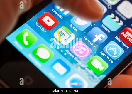 BATH, Royaume-Uni - 15 janvier 2014: un Apple iPhone 4s écran avec un pouce humain planant au-dessus de l'Facebook Banque D'Images
