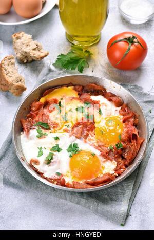 Le petit-déjeuner, oeufs au plat avec les tomates, le salami et le bacon dans la poêle Banque D'Images