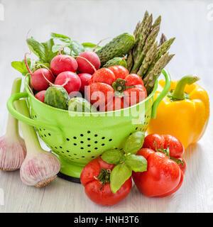 Des légumes frais dans une passoire verte avec de l'eau gouttes Banque D'Images