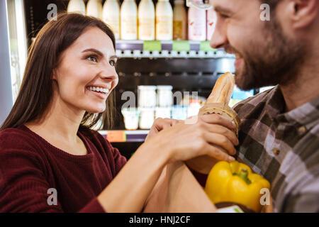 Closeup of smiling young couple with packet de nourriture à faire leurs achats dans un magasin de produits Banque D'Images