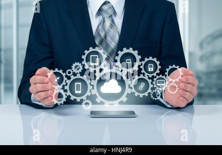 Businessman holding a cloud connecté à de nombreux objets sur un écran virtuel concept a propos de l'internet des objets.