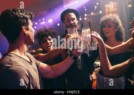 Heureux les jeunes amis en bar with cocktails. Groupe d'hommes et de femmes au célèbre discothèque avec boissons. Banque D'Images