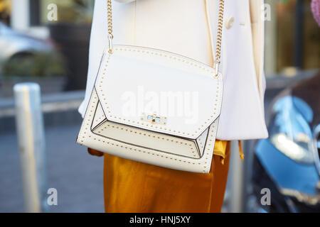 4f44a1bbdabf MILAN - janvier 14   Femme avec sac en cuir blanc avec clous et pantalon  satin