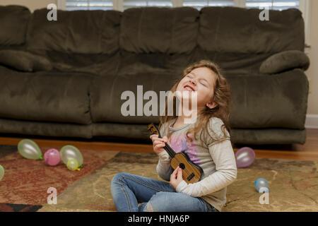 Petite fille jouant un ukulele dans son salon-de-chaussée Banque D'Images