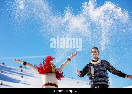 Bataille de boules de neige. Couple d'hiver jouent dans la neige à l'extérieur. Les jeunes heureux joyeux couple Banque D'Images