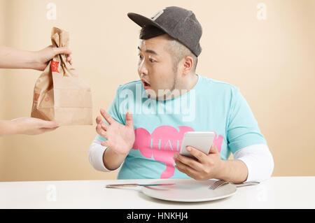 Le petit gros homme est attiré à l'alimentation Banque D'Images