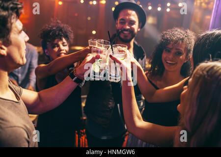 Groupe d'amis ayant des boissons au night club party. Les jeunes bénéficiant d'un bar à cocktails de brunissage. Banque D'Images