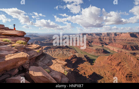 Un jeune randonneur est debout sur le bord d'une falaise offrant une vue sur le célèbre fleuve du Colorado et belle Banque D'Images