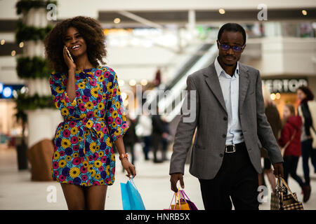 Happy afro-american couple dans un centre commercial. Girl talking on the phone Banque D'Images
