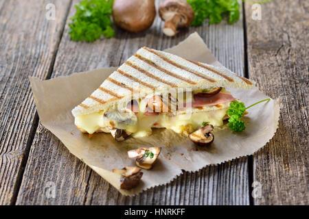 Enfoncée et double avec panini grillé jambon, fromage et champignons servi sur du papier sandwich sur une table Banque D'Images