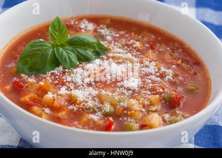 Minestrone avec du fromage parmesan râpé et de feuilles de basilic dans une assiette blanche libre. Banque D'Images