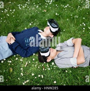 Mixed Race brother and sister laying in grass portant des lunettes de réalité virtuelle Banque D'Images