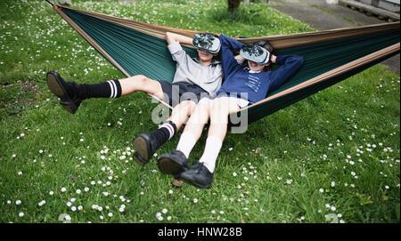 Mixed Race frère et sœur en portant des lunettes de réalité virtuelle hamac Banque D'Images