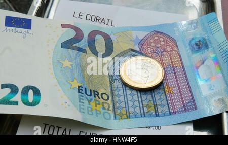 Une facture payée avec billets et pièces de monnaie dans un café parisien Banque D'Images
