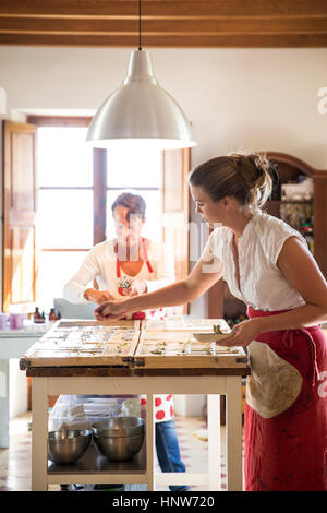 Young woman applying lavande séchées à des savons faits à la main dans l'atelier de savon Banque D'Images