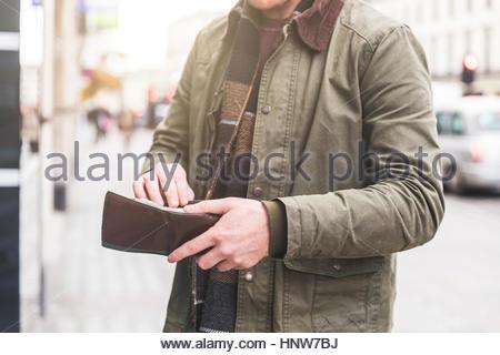 Contrôle de l'homme portefeuille dans l'avant du magasin, London, UK Banque D'Images