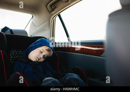Jeune garçon endormi in back seat of car Banque D'Images
