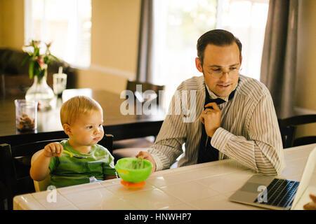 Le père et le jeune fils à table de cuisine, son eating breakfast, père de mettre sur collier, looking at laptop Banque D'Images