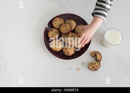Jeune garçon en tenant la plaque de biscuits fraîchement cuits au four, vue aérienne, close-up Banque D'Images