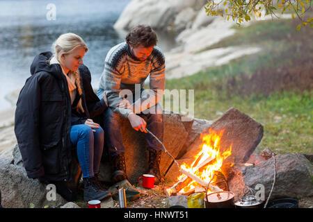 Couple sitting by campfire sur Lakeshore Banque D'Images