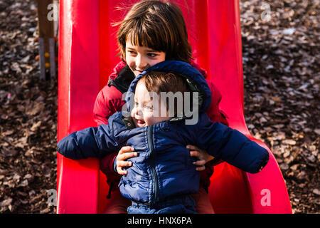 Boy holding baby brother sur l'aire de glisse