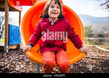 Garçon assis sur l'orange jeux Faites glisser