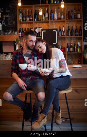 Couple assis côte à côte sur des tabourets dans cafe, tête sur l'épaule