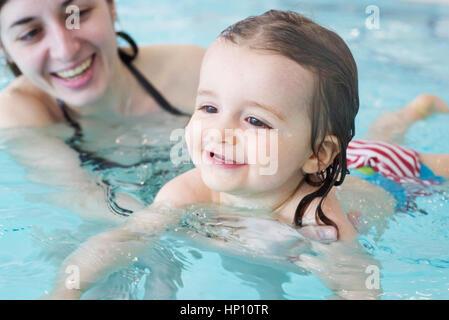 Petite fille apprendre à nager avec l'aide d'un des parents Banque D'Images
