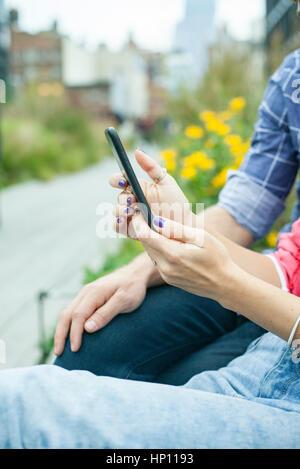 En utilisant deux smartphone outdoors, portrait Banque D'Images