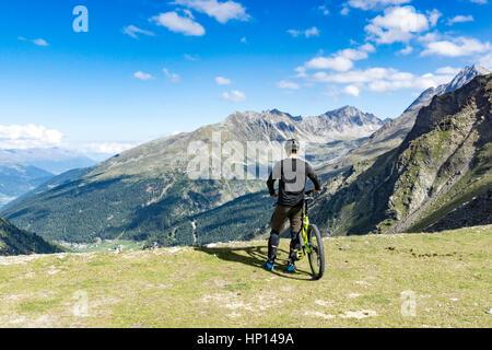 Vélo de montagne se dresse sur une jante d'un sommet et jouit de la vue sur les alpes Banque D'Images