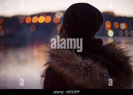 Girl traveler enjoying view de la soirée ville se reflétant dans la rivière Banque D'Images